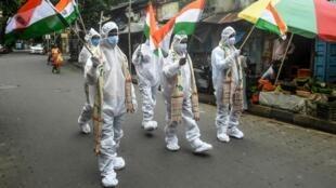 A Kolkata, en Inde, des personnels de santé défilent en tenue de protection, lors des commémorations de l'Indépendance le 15 août 2020. La propagation de l'épidémie dans ce pays très peuplé inquiète de nombreux experts.