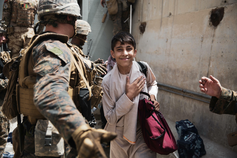 2021年8月18日,一個逃難的阿富汗男孩進入美軍控制的阿富汗機場內露出笑容。