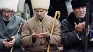 Пожилые чеченцы молятся в центральном сквере Грозного во время манифестации в поддержку Джохара Дудаева, 19 декабря 1994.
