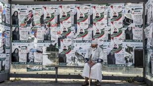Un hombre sentado en una marquesina de autobús cubierta de carteles electorales en Argel, el 11 de junio de 2021, la víspera de elecciones legislativas