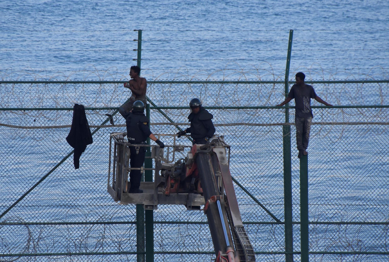 Nhiều dân nhập cư trái phép còn mắc kẹt trên cao khi tìm cách vượt tường rào ở Ceuta, thuộc Tây Ban Nha ở Bắc Phi.
