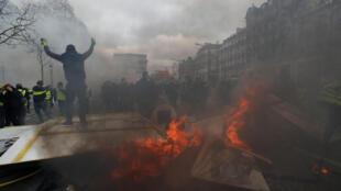 Manifestante incendeia barricada na avenida Champs-Elysées em Paris.