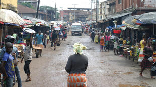 A woman walks down Bombay street in Freetown, 4 November 2014