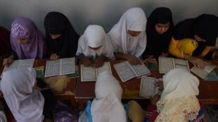 Des jeunes écolières étudient le Coran dans une madrasa, une école coranique au Pakistan.