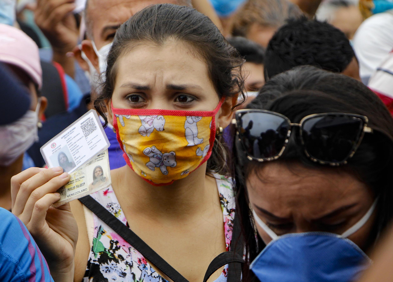 Una mujer procedente de Venezuela muestra su documentación en el fronterizo Puente Internacional Simón Bolívar, en Cúcuta, Colombia, el 12 de marzo de 2020