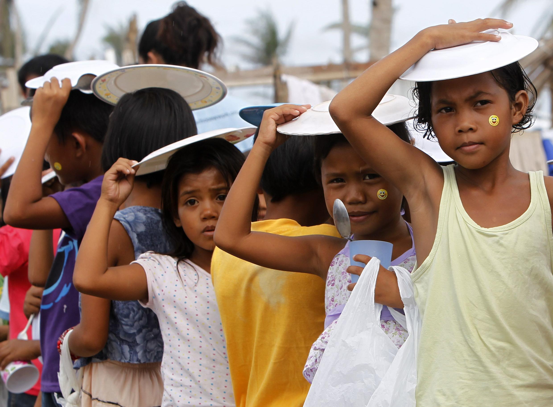 Dans la province de Leyte, le 24 décembre 2013, des enfants font la queue en attendant une distribution de nourriture.