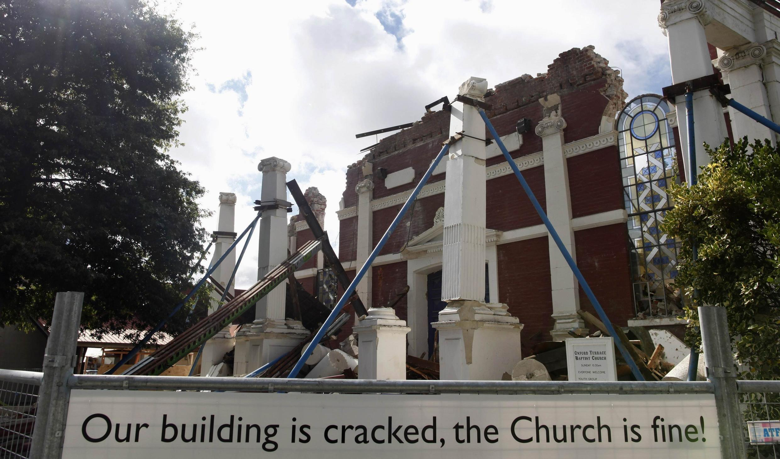 A sign referring to a previous earthquake stands in front of the destroyed Oxford Terrace Baptist church in Christchurch