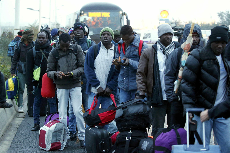 Migrantes esperando los buses que los llevan desde Calais a otras ciudades de Francia