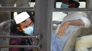 Men in facemasks wait on a bus taking them to a quarantine facility after they attended an Islamic gathering which has turned out to be a hotspot for Coronavirus infections in Nizamuddin, New Delhi