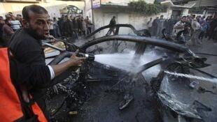 Un hombre apaga el fuego tras el ataque aéreo israelí, el 14 de noviembre de 2012 en Gaza.