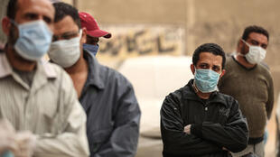 Egyptian men wait outside a food bank, after movement restrictions imposed to fight coronavirus crippled already precarious livelihoods