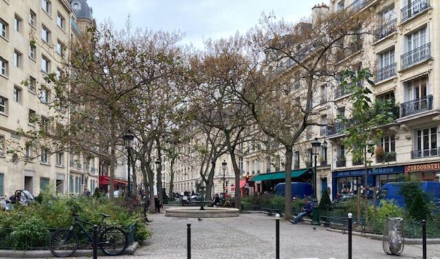 """A Praça da Estrapade, com a livraria Portuguesa e Brasileira à direita, e o restaurante """"Terra Nera"""" e a padaria """"Moderne"""" ao fundo."""