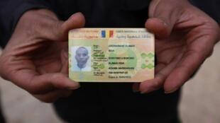 Depois de capturar um inimigo em Ajdabiyah, rebelde exibe carteira de identidade de um mercenário do Chade recrutado por Kadafi.