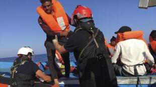Uno de los 47 migrantes rescatados en aguas del mar Mediterráneo cuando navegaban a la deriva en una barcaza de madera es ayudado por un miembro de la tripulación del Ocean Viking, el 30 de junio de 2020 a unos 55 km de la isla italiana de Lampedusa