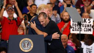 本周六 情到之處的特朗普在政治集會上擁抱一名支持者的圖片