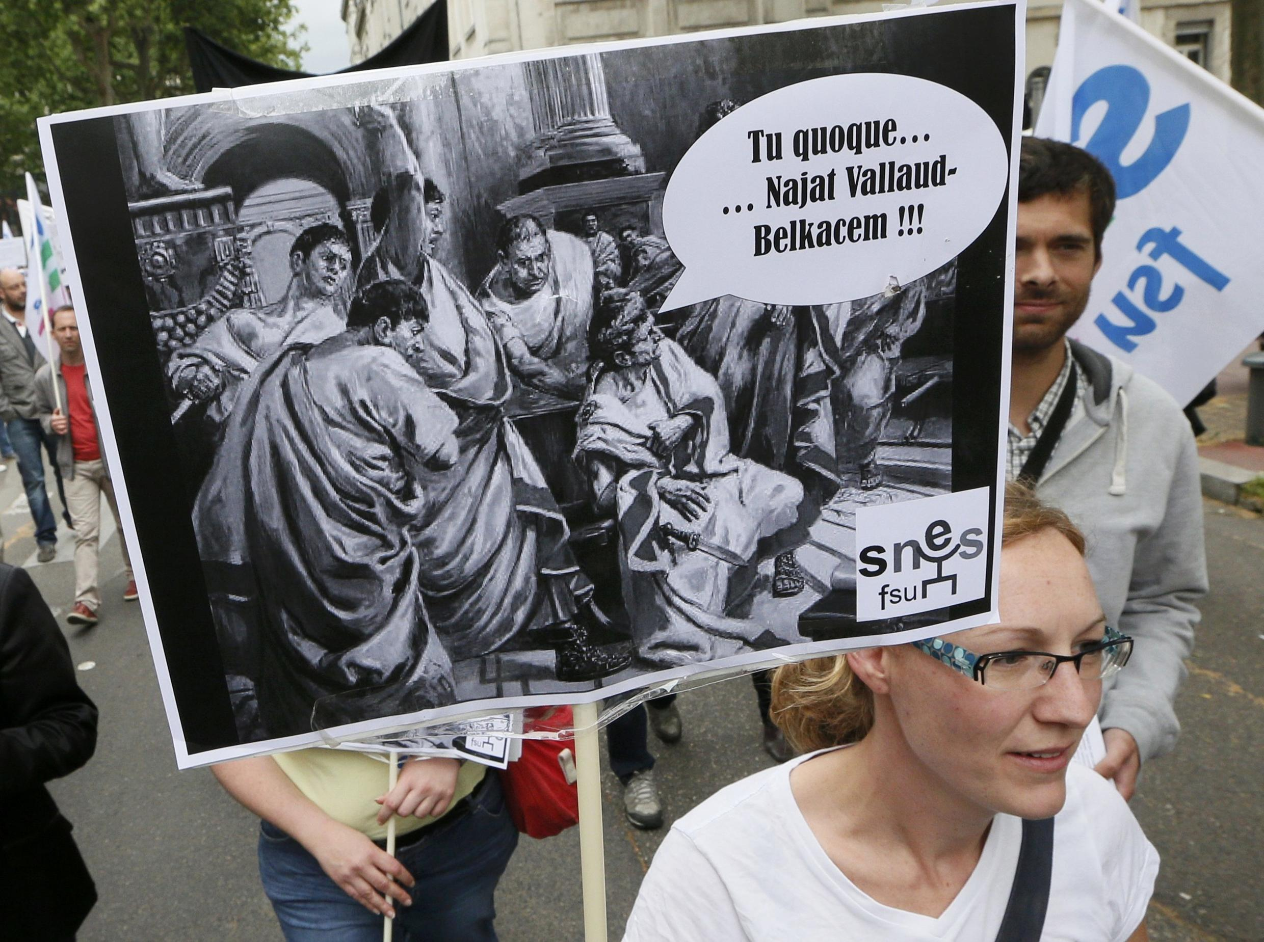 """A striking French teacher carries a placard which reads in Latin, """"And you... Najat Vallaud-Belkacem"""", in reference to the French Education Ministers, as they attend a nation-wide protest against new measures aimed at revamping the country's school system"""