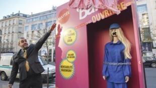"""与中国劳工观察组织合作的法国非政府组织是""""人民团结""""(Peuples Solidaires)组织在巴黎大商店前推出的""""芭比女工""""娃娃身着工作服"""