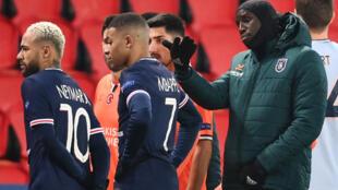 El delantero francés del Basaksehir, Demba Ba (dcha) junto a los jugadores del París Saint-Germain Neymar y Kylian Mbappé tras la suspensión del partido  de la Champions en París, el 8 de diciembre de 2020