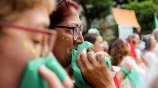 Uma mulher reage ao lado de outros participantes de uma manifestação durante o Dia Internacional da Mulher em Buenos Aires, Argentina, 8 de março de 2020.