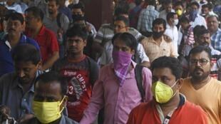 Des passagers munis de masques pour juguler la propagation du Covid-19 à la gare de Calcutta, le 21 mars 2020.