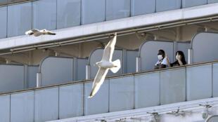 """Passageiros em uma varanda do navio de cruzeiro """"Diamond Princess"""", ancorado ao largo de Yokohama, no Japão."""