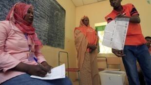 苏丹选举委员会成员向一位观察员展示选举名单17042010