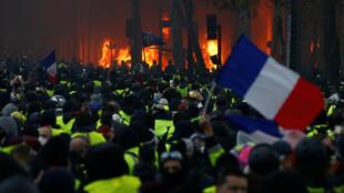 """Incêndio na praça de L'Étoile, em Paris, ao lado de manifestantes da mobilização dos """"coletes amarelos"""", em 1° de dezembro de 2018."""