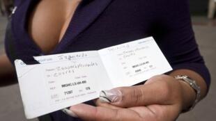 Au Venezuela, une femme tient le certificat que lui a donné la compagnie française PIP afin de lui garantir la qualité de ses prothèses mammaires.