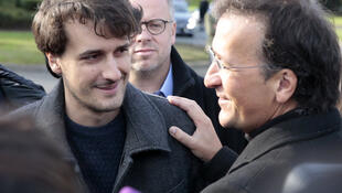 Le journaliste français Loup Bureau avec son père Loïc (à droite) et le secrétaire général de l'association Reporter sans frontières, Christophe Deloire (arrière-plan), dimanche 17 septembre 2017 à Roissy, jour de son retour de Turquie.