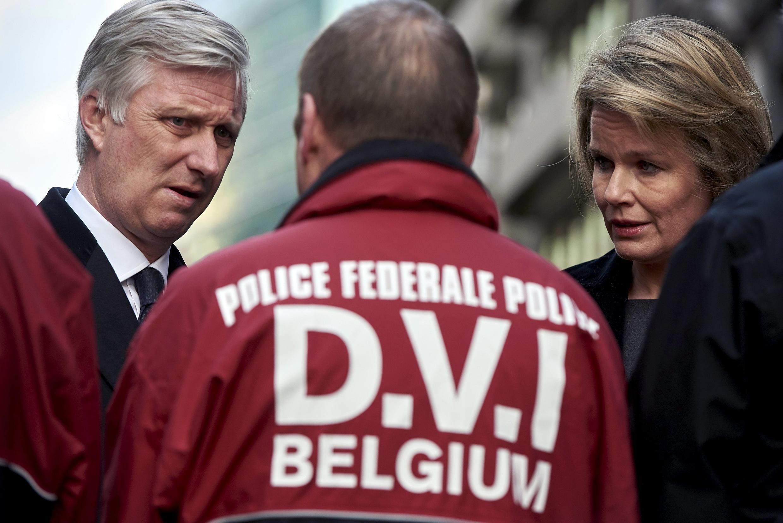 O rei Philippe e a rainha Mathilde, da Bélgica, conversam com agente de segurança após os atentados no centro de Bruxelas.
