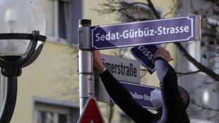 Un homme met une pancarte portant le nom de Sedat Gürbüz, propriétaire d'un bar à chicha et l'une des victimes de la fusillade meurtrière de 2020 à Hanau, en Allemagne, lors d'un hommage à l'attaque, le 19 février 2021