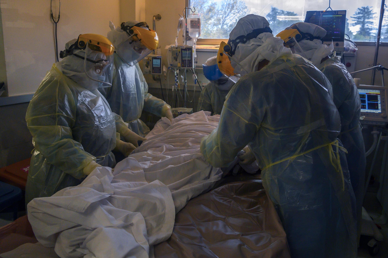 Trabajadores de la salud atienden a un paciente en una Unidad de Cuidados Intensivos (UCI) de covid-19 en un hospital privado de Montevideo el 20 de abril