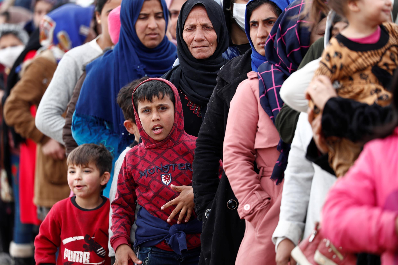 Des migrants font la queue pour recevoir de l'aide alimentaire au poste frontière turc de Pazarkule avec la Grèce Kastanies, près d'Edirne en Turquie, le 5 mars 2020.