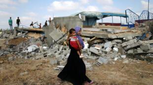 Moradores de Khan Younis, na Faixa de Gaza, observam escombros após bombardeios da aviação israelense, em 9 de agosto.