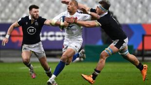 El centro francés Gael Fickou (C) intenta escapar al tackle de los escoceses  Jamie Ritchie (D) y escocés Ali Price (I), en partido del torneo de rugby de las Seis Naciones jugado el 26 de marzo de 2021, en el Stade de France de Saint-Denis