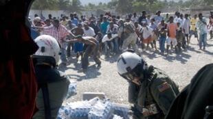Des Haïtiens se jettent littéralement sur les bouteilles d'eau qui leur sont distribuées par les soldats américains, à Port-au-Prince, le 16 janvier 2010.