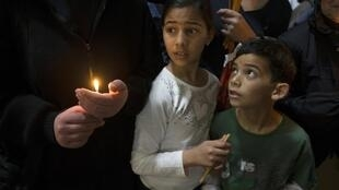 Children look at a nun holding a candle during the Catholic Washing of the Feet ceremony in the Church of the Holy Sepulchre, Jerusalem, 28 March
