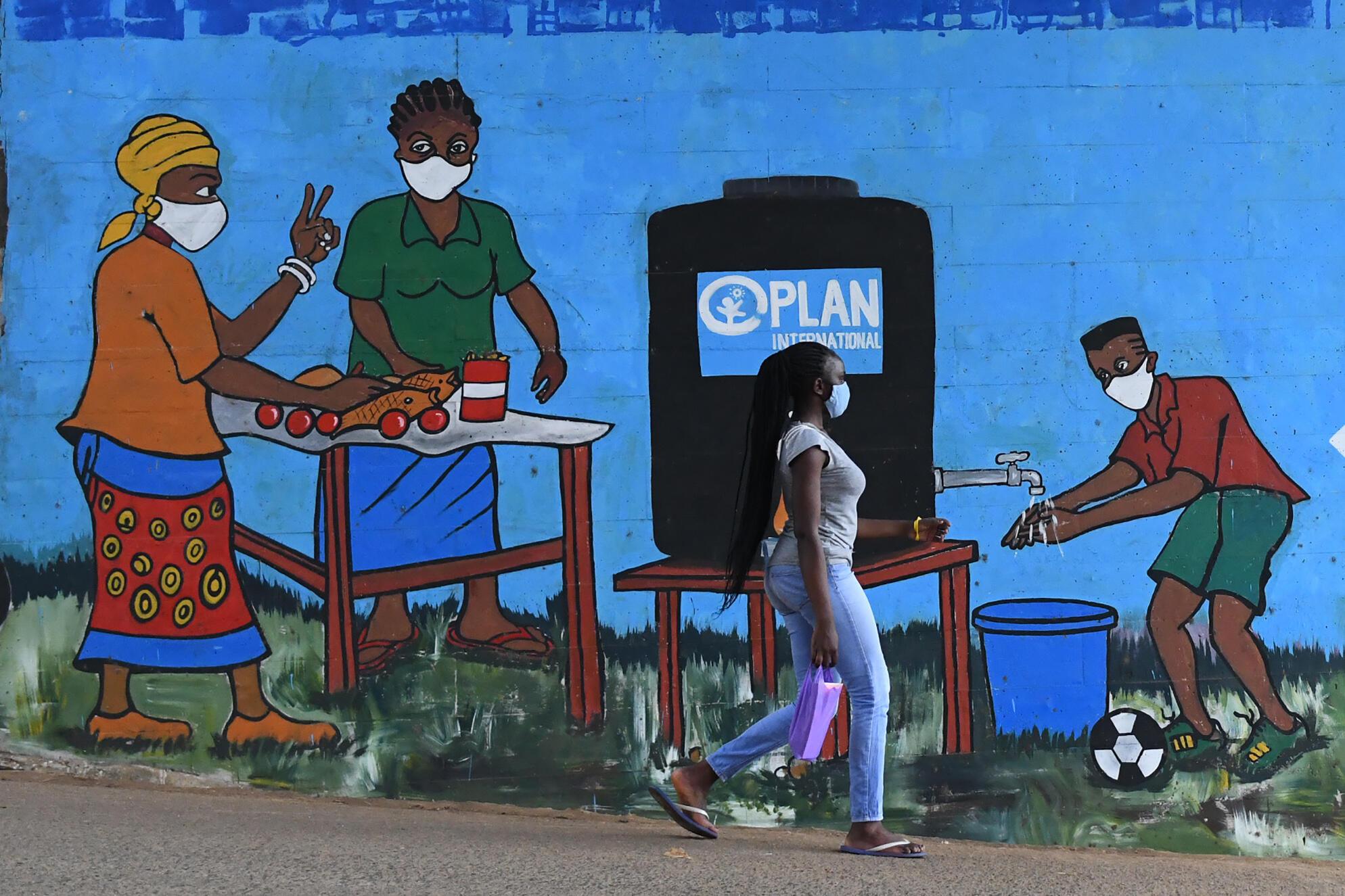 Une fresque murale encourage le lavage des mains et le port de masques comme mesures de prévention contre le coronavirus, dans le bidonville de Kibera à Nairobi, le 13 août 2020.