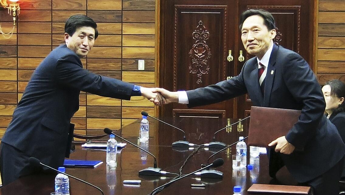 Líder da delegação norte-coreana Park Yong Il (à esq.) cumprimenta o responsável pela delegação sul-coreana, Lee Duk-haeng, durante encontro nesta quarta-feira.