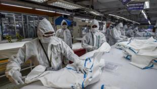 Des ouvriers de Beximco confectionnent des équipements de protection, dans une usine de Dacca, le 18 juin 2020.