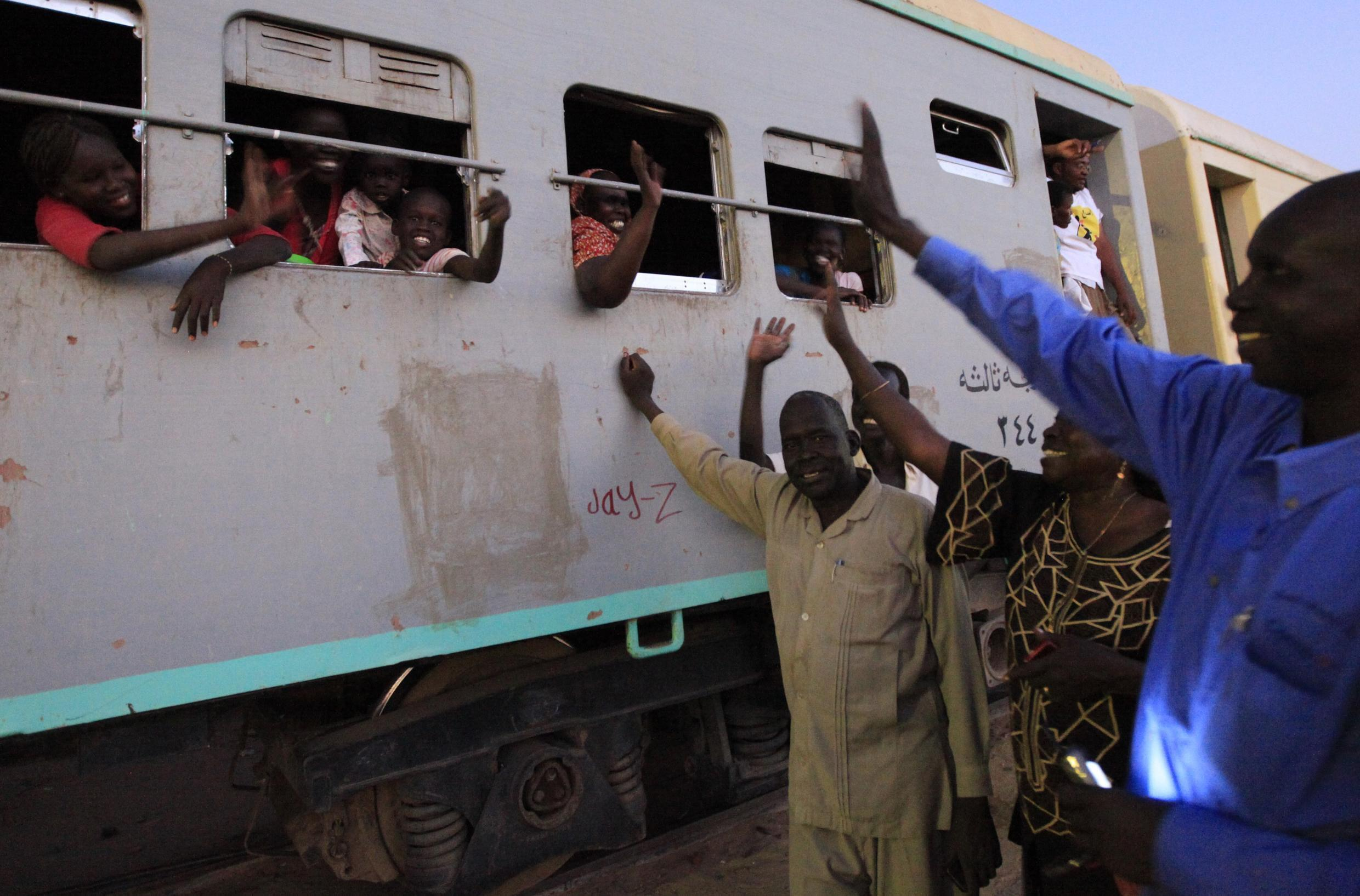 A Southern Sudanese family wave at their relatives from a train as they travel to South Sudan, in Khartoum