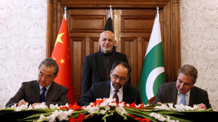 REFILE - CORRECTING ACTION Afghanistan's Foreign Minister Salahuddin Rabbani (sitting-C), Pakistan's Foreign Minister Shah Mehmood Qureshi and Chinese Foreign Minister Wang Yi sign a memorandum of understanding on cooperation in fighting terrorism in Kabul