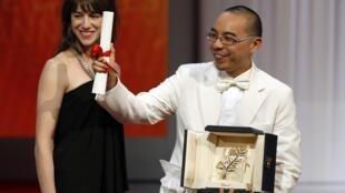 Apichatpong Weerasethakul nhận giải Cành cọ vàng từ tay nữ diễn viên Charlotte Gainsbourg (©Reuters)