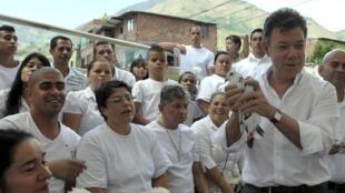 Juan Manuel Santos tenant un oiseau (un pigeon et non une colombe) dans les mains, à Bello le 28 août 2012.