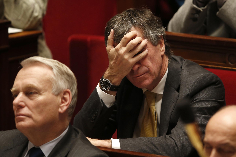 O ministro Jérôme Cahuzac, em segundo plano atrás do premiê Jean-Marc Ayrault, reage com irritação às acusações de que teve uma conta bancária não declarada na Suíça.
