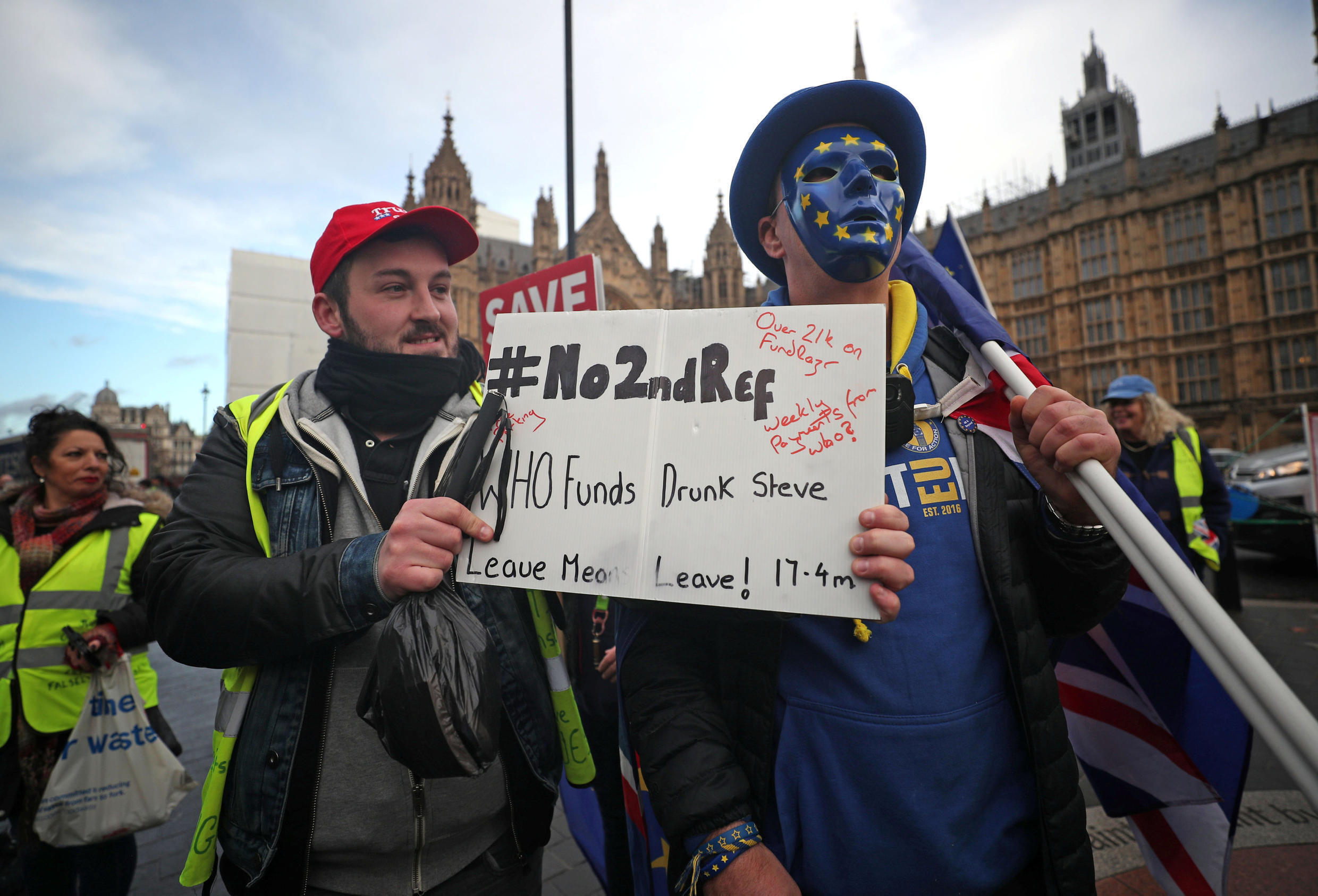 """British """"Yellow Vests UK"""" demonstrator James Goddard holds a placard in front of a pro-EU demonstrator outside the Houses of Parliament in London, 19 December 2018."""
