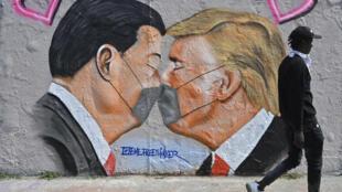 Una pintura mural del artista Eme Freethinker representa al presidente chino, Xi Jinping (izq), y al estadounidense, Donald Trump, saludándose cariñosamente con mascarilla, en una imagen tomada el 28 de abril de 2020 en Berlín