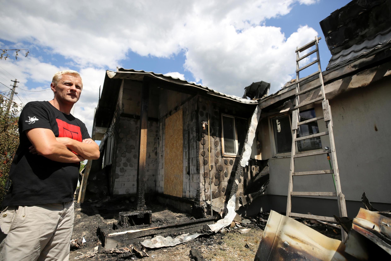 Le militant ukrainien anticorruption Vitaliy Chabounine à côté de sa maison endommagée par un incendie, dans le village de Hnidyn dans la région de Kiev, le 23 juillet 2020.