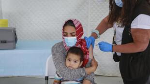 Una mujer con su hijo en brazos recibe una dosis de la vacuna contra el covid-19 en el campo de refugiados de Mavrovouni, en la isla griega de Lesbos, el 3 de junio de 2021