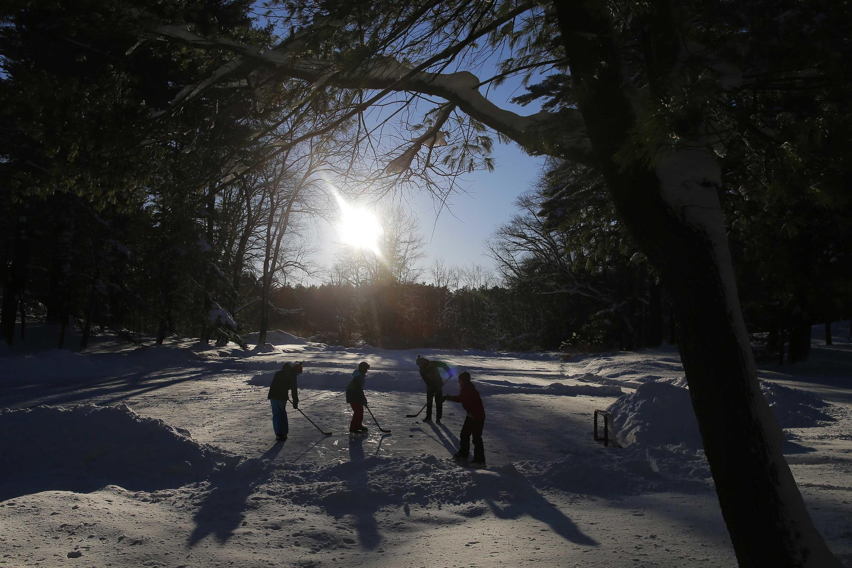 Crianças jogam hóquei em um lago congelado em Boxford, Massachusetts, após a tempestade de neve que atingiu o nordeste dos EUA nesta sexta-feira, 3 de janeiro de 2014.